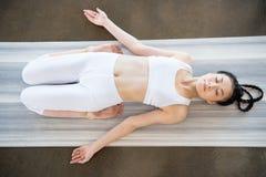 Młoda azjatykcia kobieta robi Opierający bohater pozę Supta Virasana na joga macie zdjęcie royalty free
