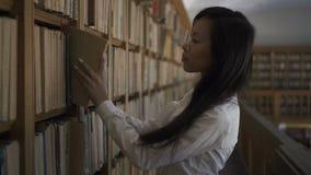 Młoda azjatykcia kobieta stawia książkę na półce w round szkłach zbiory wideo