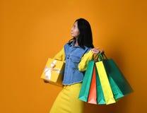 Młoda azjatykcia kobieta z torbami na zakupy na koloru tle zdjęcia royalty free