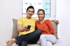 Młoda azjatykcia kochająca para relaksuje telewizję i ogląda Obrazy Stock