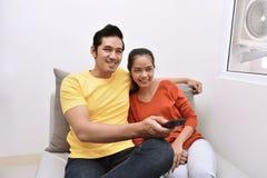 Młoda azjatykcia kochająca para relaksuje telewizję i ogląda Obraz Stock