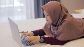 Młoda azjatykcia muzułmańska kobieta kłaść w dół na łóżkowym używa laptopie zbiory