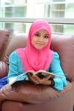 Młoda azjatykcia muzułmańska kobieta w kierowniczego szalika uśmiechu czytelniczym magazynie Zdjęcie Stock