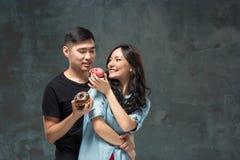 Młoda azjatykcia para cieszy się łasowanie słodki kolorowy pączek Zdjęcia Stock