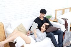 Młoda azjatykcia para patrzeje mądrze pastylkę szukać dla planu podróży, książkowego pokoju hotelowego, zakupu bileta lub zakup p obraz stock