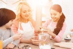 Młoda babcia i wnuki łamamy jajka w puchar w kuchni Llittle dziewczyna uczy się gotować Fotografia Royalty Free