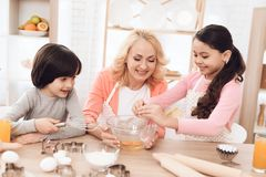 Młoda babcia i wnuki łamamy jajka w puchar w kuchni Llittle dziewczyna uczy się gotować Obrazy Stock