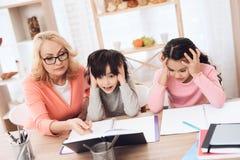 Młoda babcia pomaga robić lekcjom dla wnuków Piękni babć pomocy dzieci uczą się Zdjęcie Stock