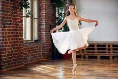 Młoda balerina w białego spódniczka baletnicy ćwiczy tanu rusza się zdjęcia stock