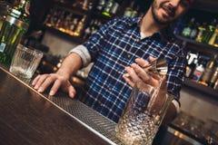 Młoda barman pozycja przy baru kontuaru dolewania alkoholem w szkło od osadzarki szczęśliwej w górę fotografia stock