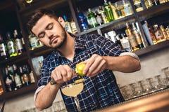 Młoda barman pozycja przy baru kontuaru wapna tnącym zapałem w coktail koncentrującego obraz royalty free