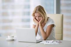 Młoda beznadziejna kobieta przy laptopem zdjęcie stock