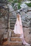 Młoda biała pixie królowa w koronie z przesłoną i długi ubieramy puszek kamienni schodki w bajecznie lokaci fotografia royalty free
