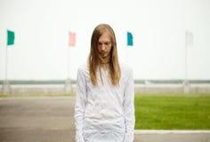 Młoda biały człowiek pozycja przy parkiem z smutną twarzą i zamykającymi oczami Fotografia Stock