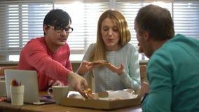Młoda biznes drużyna bierze przerwę od pracy i je pizzę zbiory wideo
