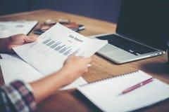 młoda biznesmen kobieta wręcza przeglądać analizujący pieniężnego data zdjęcia stock