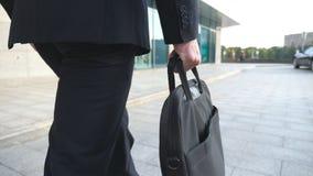 Młoda biznesmena mienia teczka w ręce i odprowadzenie w mieście Biznesowy mężczyzna dojeżdżać do pracy pracować Ufny facet w kost obrazy royalty free