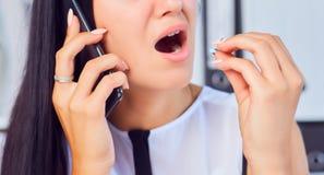 Młoda biznesowa kobieta bierze medycynę w stresującej sytuaci przy miejscem pracy Kobieta konsultuje na telefonie z jej lekarką obrazy stock