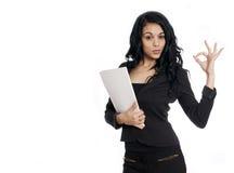 Młoda biznesowa kobieta daje OK znakowi trzyma falcówkę Obrazy Stock