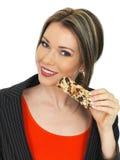 Młoda Biznesowa kobieta Je Śniadaniowego zboża baru Fotografia Royalty Free