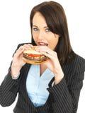 Młoda Biznesowa kobieta Je wołowina hamburger Obrazy Stock