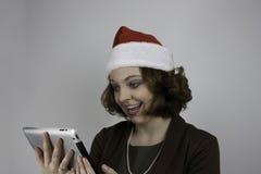 Młoda biznesowa kobieta jest ubranym Santa kapelusz i używa pastylkę Fotografia Stock