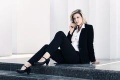 Młoda biznesowa kobieta opowiada na telefonie komórkowym przy budynkiem biurowym obrazy royalty free