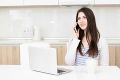 Młoda biznesowa kobieta opowiada na telefonie podczas gdy siedzący przy stołem ilustracji
