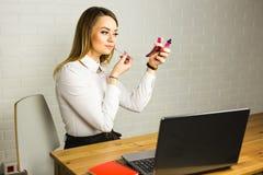 Młoda biznesowa kobieta patrzeje w lustrze i używa pomadkę przy jej worlplace Fotografia Stock
