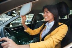 Młoda biznesowa kobieta patrzeje w lustrze podczas gdy jadący samochód Obrazy Royalty Free