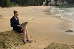 Młoda biznesowa kobieta pracuje na jej laptopie przy plażą Zdjęcia Stock