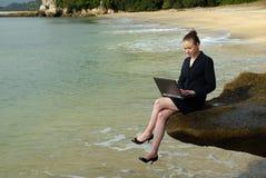 Młoda biznesowa kobieta pracuje na jej laptopie przy plażą Fotografia Royalty Free