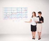 Młoda biznesowa kobieta przedstawia rynku papierów wartościowych diagram Zdjęcie Royalty Free