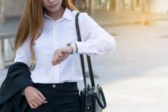 Młoda biznesowa kobieta sprawdza czas na jej zegarku fotografia royalty free