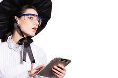 Młoda biznesowa kobieta używa pastylka peceta i będący ubranym szkła i futurystycznego kapelusz Zdjęcia Stock