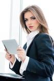 Młoda biznesowa kobieta używa pastylka peceta przy jej biurem podczas gdy stojący zrelaksowanego pobliskiego okno fotografia stock