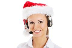 Młoda biznesowa kobieta w kapeluszu, mikrofonie i hełmofonach Santa. Fotografia Stock