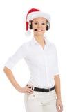 Młoda biznesowa kobieta w kapeluszu, mikrofonie i hełmofonach Santa. Zdjęcie Royalty Free