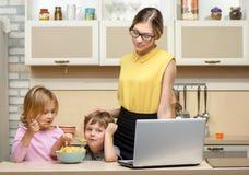 Młoda biznesowa kobieta w kuchni z jej małym Zdjęcia Stock