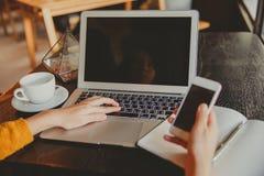 Młoda biznesowa kobieta wręcza używać smartphone podczas gdy pracujący na c zdjęcia royalty free
