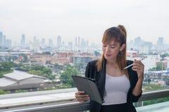 Młoda biznesowa kobieta z pastylką w biurze przeciw panoramicznemu Fotografia Stock