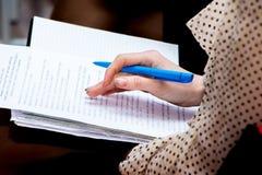 Młoda biznesowa kobieta z piórem w jego ręce zauważa znacząco infor zdjęcie royalty free
