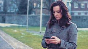 Młoda biznesowa kobieta z smartphone na zewnątrz biura zdjęcie wideo