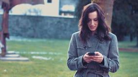 Młoda biznesowa kobieta z smartphone na zewnątrz biura zbiory
