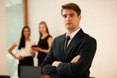 Młoda Biznesowego mężczyzna pozycja w pierwszy równinie z coworkers w b Obrazy Royalty Free
