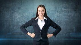 Młoda biznesowej kobiety suknia w czarnym kostiumu i białej koszula stoi, trzymający jej ręki na biodrach z copyspace Zdjęcie Royalty Free