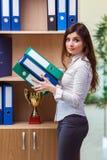 Młoda bizneswoman pozycja obok półki fotografia stock