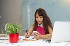 Młoda bizneswomanu gmerania informacja na mądrze telefonie obrazy stock