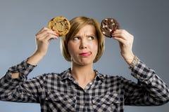 Młoda blond śliczna i życzliwa caucasian kobieta trzyma dwa dużego czekoladowego ciastka w przypadkowych ubraniach obrazy stock