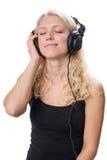 Młoda blond dziewczyna jest ubranym hełmofony i cieszy się muzykę Zdjęcia Stock